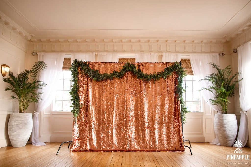 large photo booth backdrop with floral garland